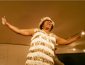 Queen Latifah as Bessie Smith, in a black and blue dress...