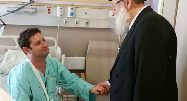 Chief Rabbi Stern holds the hand of one Pride victim (Chief Rabbi Aryeh Stern/Facebook)