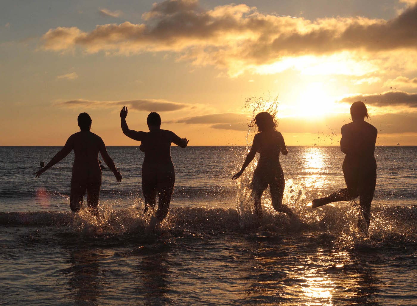 Nudists take part in the annual North East Skinny Dip as the sun rises at Druridge Bay in Northumberland, northeast England on September 22, 2013. Around 200 bathers once again braved the cold in an attempt to break the world record for the largest skinny-dip. AFP PHOTO / LINDSEY PARNABY (Photo credit should read LINDSEY PARNABY/AFP/Getty Images)