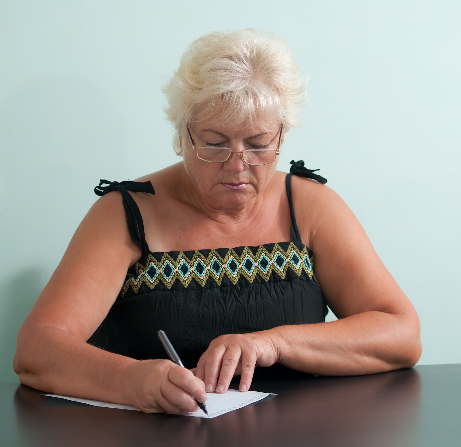 Mature woman with glasses writing a letter.