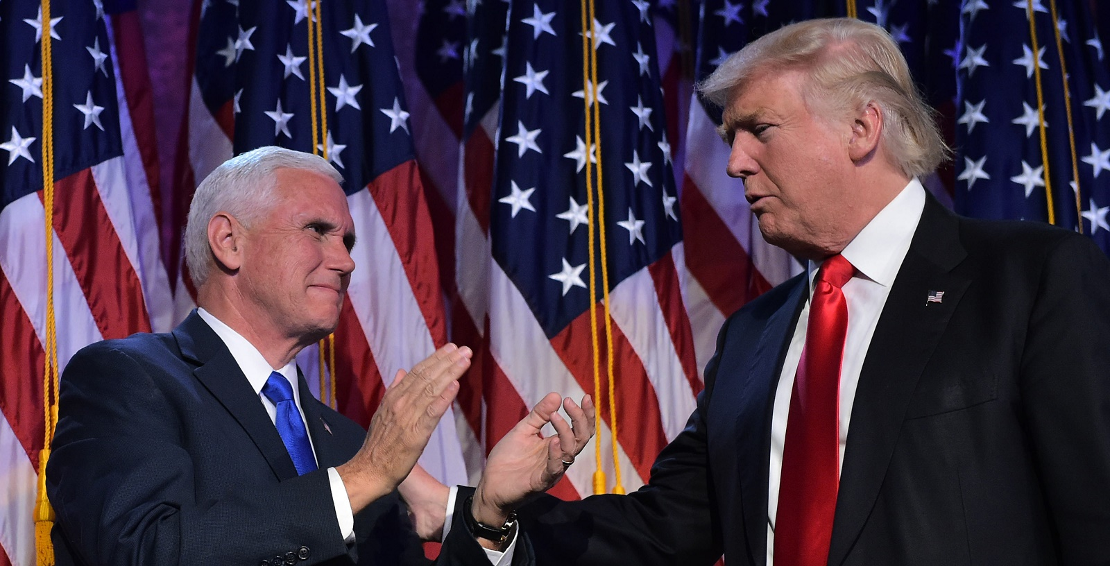Republican presidential elect Donald Trump (R) reaches to his Vice President elect Mike Pence during election night at the New York Hilton Midtown in New York on November 9, 2016. Trump stunned America and the world Wednesday, riding a wave of populist resentment to defeat Hillary Clinton in the race to become the 45th president of the United States. / AFP / MANDEL NGAN (Photo credit should read MANDEL NGAN/AFP/Getty Images)