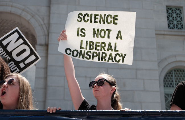 A protester at the March for Science holds up a sign reading 'science is not a liberal conspiracy'