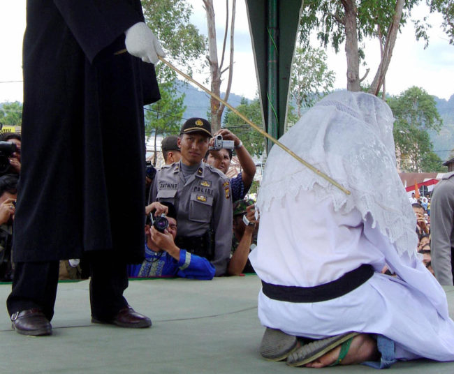 TAKENGON, INDONESIA: An Acehnese executor flogs a convicted woman in Takengon, in Indonesian central Aceh province, 19 August 2005 after an Islamic sharia court ordered four women to be flogged for petty gambling offences. The public lashing was the second since the Indonesian government allowed the western province to implement religious law as part of broader autonomy granted in 2001 to curb a separatist Islamist insurgency. AFP PHOTO (Photo by STR/AFP/Getty Images)