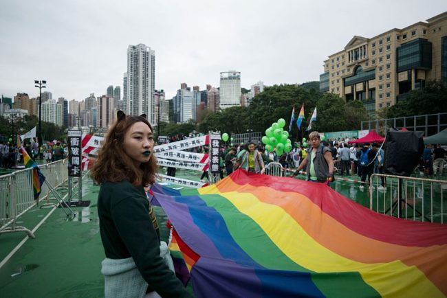 A participant of Hong Kong's annual pride parade stands next to a large rainbow flag on November 26, 2016.  A huge rainbow flag led thousands through the streets of Hong Kong on November 26 as the city's LGBT community braved the rain and wind to call for equality at its annual pride parade. / AFP / Aaron TAM        (Photo credit should read AARON TAM/AFP/Getty Images)