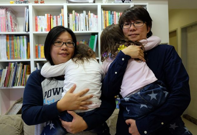 Same-sex parents Hope Chen (L), 37, and Zoro Wen, 34, posing with their twin daughters