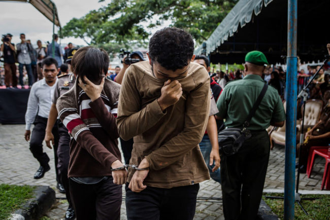 BANDA ACEH, INDONESIA - MAY 23: Indonesian gay couple walk as arrive for caning in public from an executor known as 'algojo' for having gay sex, which is against Sharia law at Syuhada mosque on May 23, 2017 in Banda Aceh, Indonesia. The two young gay men, aged 20 and 23, were caned 85 times each in the Indonesian province of Aceh during a public ceremony after being caught having sex last week. It was the first time gay men have been caned under Sharia law as gay sex is not illegal in most of Indonesia except for Aceh, which is the only province which exercises Islamic law. The punishment came a day after the police arrested 141 men at a sauna in the capital Jakarta on Monday due to suspicion of having a gay sex party, the latest crackdown on homosexuality in the country. (Photo by Ulet Ifansasti/Getty Images)
