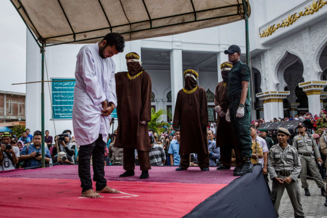 BANDA ACEH, INDONESIA - MAY 23: An Indonesian man gets caning in public from an executor known as 'algojo' for having gay sex, which is against Sharia law on May 23, 2017 in Banda Aceh, Indonesia. The two young gay men, aged 20 and 23, were caned 85 times each in the Indonesian province of Aceh during a public ceremony after being caught having sex last week. It was the first time gay men have been caned under Sharia law as gay sex is not illegal in most of Indonesia except for Aceh, which is the only province which exercises Islamic law. The punishment came a day after the police arrested 141 men at a sauna in the capital Jakarta on Monday due to suspicion of having a gay sex party, the latest crackdown on homosexuality in the country. (Photo by Ulet Ifansasti/Getty Images)