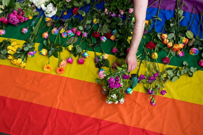 Demonstrators in London lay roses on a rainbow flag as they protest purge of gay men in Chechnya