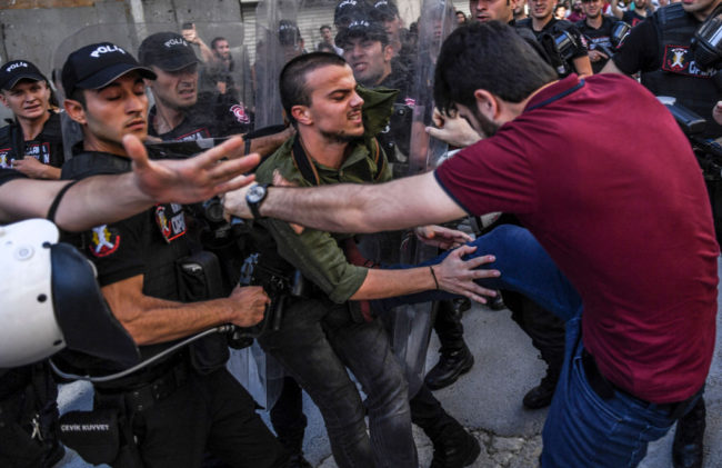 An LGBT activist is kicked by a plain-clothed police officer at banned Istanbul Pride 2017