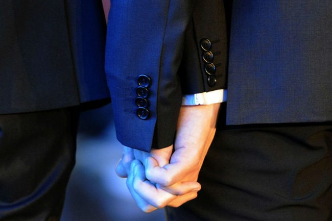 A gay couple holding hands. Two men were recently asked to leave a Wetherspoons for kissing
