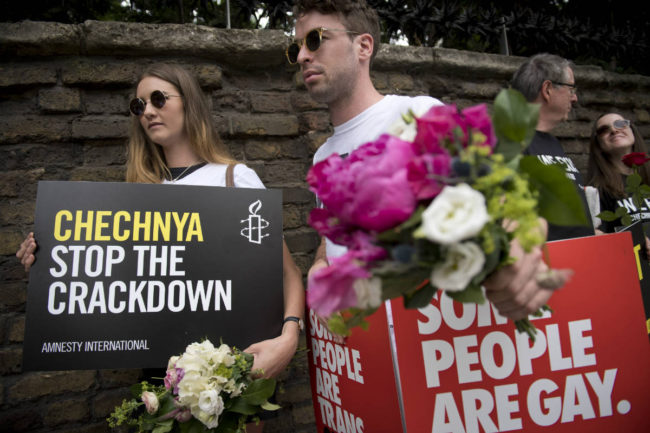 Demonstrators carry placards outside the Russian Embassy in London