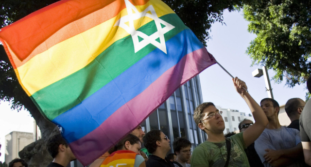 An Israeli man waves a rainbow flag bearing the Star of David - similar to that waved at the Chicago Dyke March
