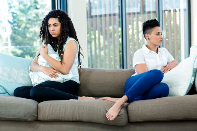 Unhappy lesbian couple sitting on sofa in living room