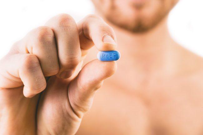 Man holding a pill used for Pre-Exposure Prophylaxis (PrEP) to prevent HIV infection