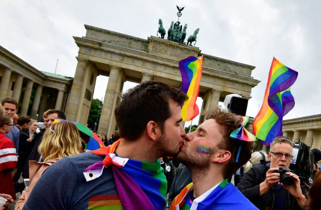 TOPSHOT - Two men kiss as they attend a rally of gays and lesbians in front of the Brandenburg Gate in Berlin on June 30, 2017. The German parliament legalised same-sex marriage, days after Chancellor Angela Merkel said she would allow her conservative lawmakers to follow their conscience in the vote. / AFP PHOTO / Tobias SCHWARZ (Photo credit should read TOBIAS SCHWARZ/AFP/Getty Images)