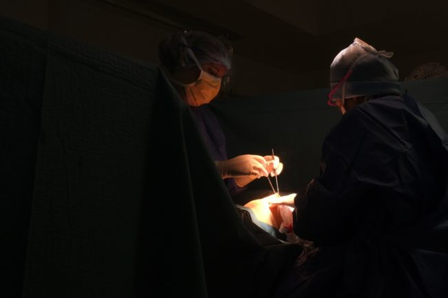 Two surgeons operate on someone in a dark room