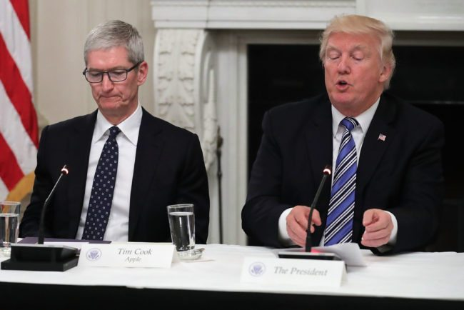 "WASHINGTON, DC - JUNE 19:  Apple CEO Tim Cook listens to U.S. President Donald Trump deliver opening remarks during a meeting of the American Technology Council in the State Dining Room of the White House June 19, 2017 in Washington, DC. According to the White House, the council's goal is ""to explore how to transform and modernize government information technology.""  (Photo by Chip Somodevilla/Getty Images)"