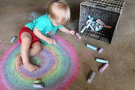 A small child draws a rainbow on the pavement