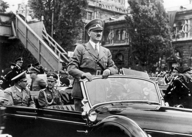 6th September 1938:  The Chancellor of Germany, Adolf Hitler (1889 -1945) standing in his car as he travels through the ancient town of Nuremberg to open the Nazi Congress. In the rear seat of the car on the left is Hitler's secretary and friend Martin Bormann (1900 - 1945).  (Photo by Keystone/Getty Images)