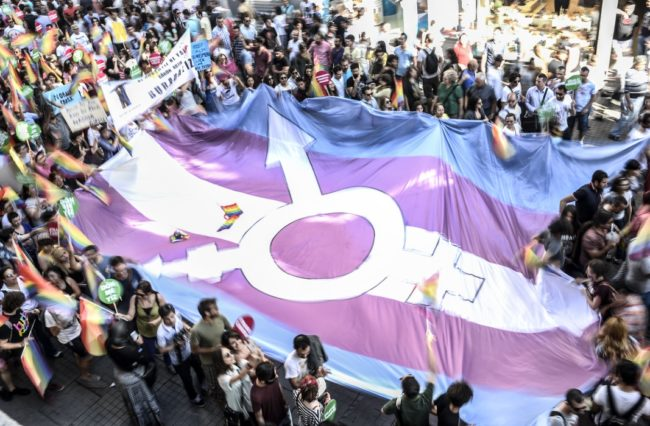 People hold a giant transgender flag during a gay parade on Istiklal Street, the main shopping corridor in Istanbul, on June 22, 2014, during the Trans Pride Parade as part of the Trans Pride Week 2014, which is organized by Istanbul's 'Lesbians, Gays, Bisexuals, Transvestites and Transsexuals' (LGBTT) solidarity organization. AFP PHOTO/BULENT KILIC