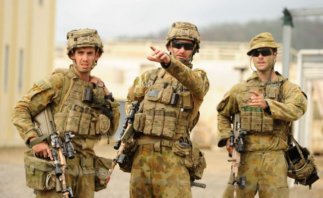 ROCKHAMPTON, AUSTRALIA - JULY 09: Australian soldiers from 7 Brigade discuss tactics as part of exercise Talisman Sabre on July 9, 2015 in Rockhampton, Australia. Talisman Sabre is a biennial military exercise that trains Australian and U.S. forces to plan and conduct combined task force operations to improve combat readiness and interoperability on a variety of missions from conventional conflict to peacekeeping and humanitarian assistance efforts. TS15 will incorporate force preparation activities, Special Forces activities, amphibious landings, parachuting, land force manoeuvre, urban operations, air operations, maritime operations and the coordinated firing of live ammunition and explosive ordnance from small arms, artillery, naval vessels and aircraft. (Photo by Ian Hitchcock/Getty Images)