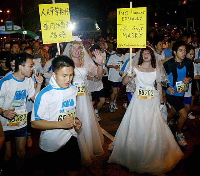 "HONG KONG, CHINA: Matt Pearce (L) and Adrian Smith (R) wearing wedding dresses and holding placards run along with thousands of participants in the 10km Men's Open race of Standard Chartered Hong Kong Marathon 2005 in Tsim Tsa Tsui district of Hong Kong, 27 February 2005. Matt and Adrian joined the marathon as a running demonstration calling on the government to allow same-sex-marriage. ""We chose the marathon because it is a middle class family event and it's that class of people who are preventing gays the right to marry,"" said Matt Pearce, protest co-ordinator and spokesman for activist group International Action. Homosexuality was only decriminalised in Hong Kong in 1991 and the age of consent for gays is 21 even though for heterosexuals it is 16. Gay marriage is still banned. Gay and lesbian groups say authorities have hardened their opposition since rule of Hong Kong was transferred in 1997 to China, where homosexuality, though lawful, is stigmatised. AFP PHOTO/TED ALJIBE (Photo credit should read TED ALJIBE/AFP/Getty Images)"