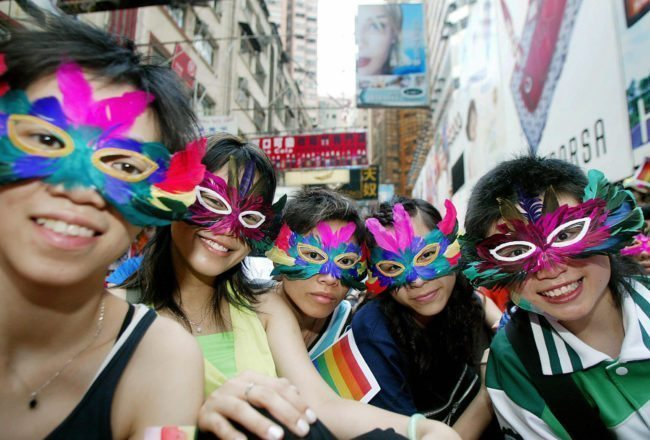 HONG KONG, CHINA:  Gay activists wearing masks attend a gathering and march in the Causeway Bay district of Hong Kong, 16 May 2005. Some 350 people from various backgrounds gathered 16 May to raise public awareness for the first time on homophobia and promote diversity.    AFP PHOTO/TED ALJIBE  (Photo credit should read TED ALJIBE/AFP/Getty Images)