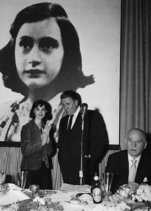 Actress Millie Perkins talking to producer George Stevens in front of a picture of holocaust victim Anne Frank, at a reception for their film 'The Diary of Anne Frank' at 20th Century Fox Studios in Hollywood, February 27th 1958. (Photo by Keystone/Hulton Archive/Getty Images)