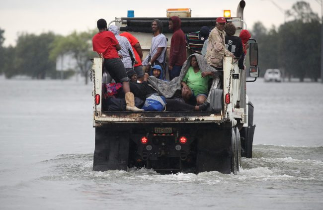 PORT ARTHUR, TX - AUGUST 30:  Evacuees ride on a truck after they were driven from their homes by the flooding from Hurricane Harvey on August 30, 2017 in Port Arthur, Texas. Harvey, which made landfall north of Corpus Christi late Friday evening, is expected to dump upwards to 40 inches of rain in Texas over the next couple of days.  (Photo by Joe Raedle/Getty Images)