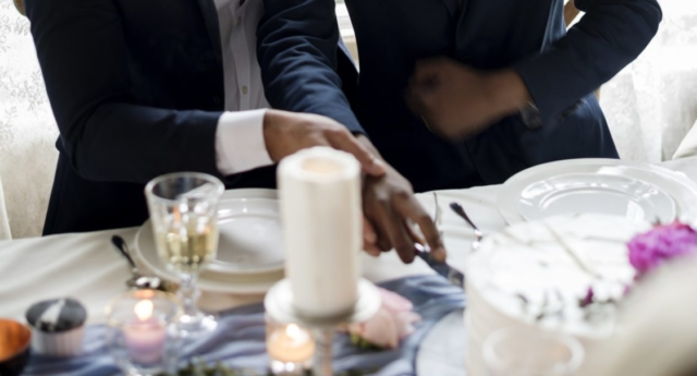 Gay Couple Cutting Cake Together on Wedding Reception (Photo: RawPixel)