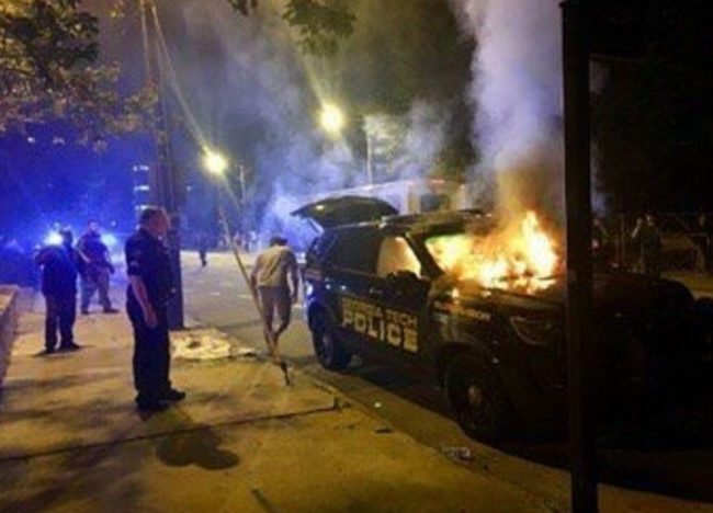 A police car on fire after the riots