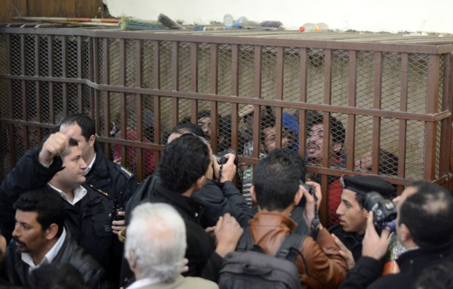 "Defendants react behind the bars at a court in Cairo following the acquittal on January 12, 2015 of 26 male men accused of ""debauchery"" after they were arrested in a night-time raid on a bathhouse in the Egyptian capital last month that triggered international concern. The men were arrested on December 7 in the raid on a hammam in the Azbakeya district of Cairo, amid fears of a widening police crackdown on homosexuals in Egypt even though Egyptian law does not expressly ban homosexuality. AFP PHOTO / MOHAMED EL-SHAHED        (Photo credit should read MOHAMED EL-SHAHED/AFP/Getty Images)"