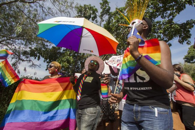 People holding rainbow flags and umbrellas take part in the Gay Pride parade in Entebbe on August 8, 2015. Ugandan activists gathered for a gay pride rally, celebrating one year since the overturning of a strict anti-homosexuality law but fearing more tough legislation may be on its way. Homosexuality remains illegal in Uganda, punishable by a jail sentence. AFP PHOTO/ ISAAC KASAMANI        (Photo credit should read ISAAC KASAMANI/AFP/Getty Images)
