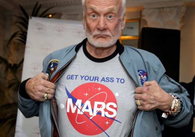 "Former NASA astronaut Buzz Aldrin shows the t-shirt he wears promoting Mars exploration on November 12, 2015 in Geneva. Aldrin attended a press conference alongside Soviet cosmonaut Alexei Leonov and Swiss astronaut Claude Nicollier on the eve of a conference in Lausanne entitled ""The Moon Race"".   AFP PHOTO / FABRICE COFFRINI        (Photo credit should read FABRICE COFFRINI/AFP/Getty Images)"