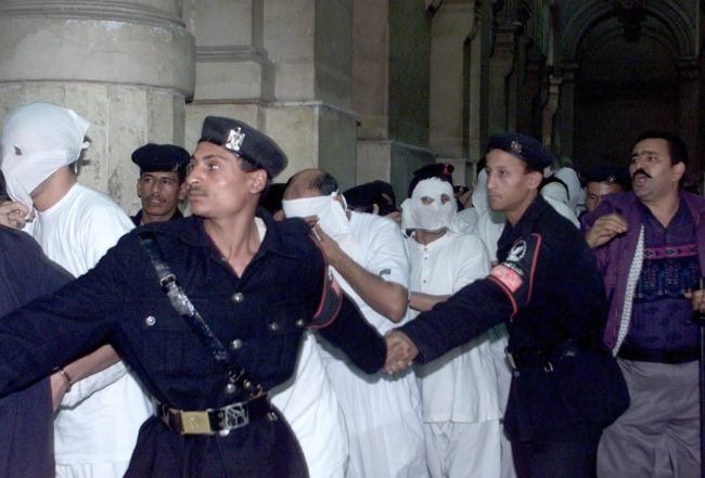 CAIRO, EGYPT:  Egyptians dressed in white with their faces covered, charged with engaging in homosexual activities and scorning Islam, enter a Cairo court under the protection of security men 14 November 2001. One of the 52 men was sentenced to five years in prison and several to three years at the end of their trial. The men were arrested in May following a party on a Nile riverboat. AFP PHOTO/Marwan NAAMANI (Photo credit should read MARWAN NAAMANI/AFP/Getty Images)