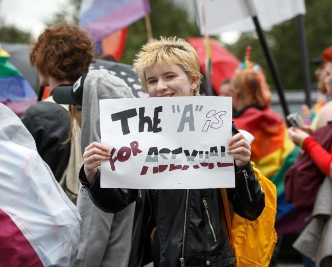 "GLASGOW, SCOTLAND - AUGUST 19: A participant holds a sign that says ""The ""A"" is for asexual"" during the Glasgow Pride march on August 19, 2017 in Glasgow, Scotland. The largest festival of LGBTI celebration in Scotland has been held every year in Glasgow since 1996. (Photo by Robert Perry/Getty Images)"