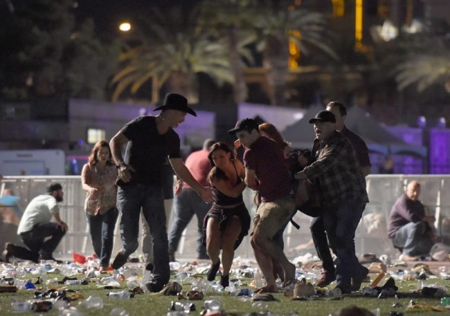 LAS VEGAS, NV - OCTOBER 01: (EDITORS NOTE: Image contains graphic content.) People carry a peson at the Route 91 Harvest country music festival after apparent gun fire was heard on October 1, 2017 in Las Vegas, Nevada. There are reports of an active shooter around the Mandalay Bay Resort and Casino. (Photo by David Becker/Getty Images)