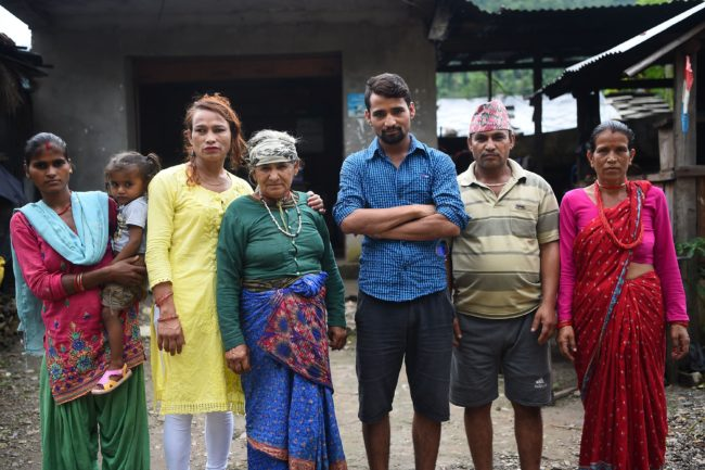 This photo taken on August 23, 2017 shows Nepali transgender person Monika Shahi Nath (3rd L) with Laxmi Giri Nath (L), the first wife of her husband Ramesh Nath Yogi (3rd R), Ramesh's youngest daughter Nabin Nath (2nd), Ramesh's grandmother-in-law Parbati Devi Nath (C), Ramesh's father-in-law Bhawani Nath (2nd) and Ramesh's mother-in-law Sita Devi Nath (R) in Kain Pani village in Nepal's Dadeldhura district. Monika Shahi Nath, 40, became Nepal's first transgender person to be issued with a marriage certificate by district officials when she married 22-year-old Ramesh Nath Yogi in May, even though Nepal has no formal laws for such unions. The couple have found a rare acceptance in Nepal, where many transgender people still struggle to be open about their identity despite progressive laws that include a third gender option on identity cards and passports. / AFP PHOTO / Prakash MATHEMA / TO GO WITH Nepal-transgender-marriage-rights        (Photo credit should read PRAKASH MATHEMA/AFP/Getty Images)