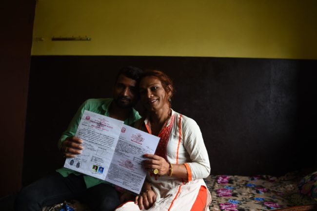 This photo taken on August 3, 2017 shows Nepali transgender person Monika Shahi Nath and her husband Ramesh Nath Yogi holding their marriage certificate in Kathmandu. Monika Shahi Nath, 40, became Nepal's first transgender person to be issued with a marriage certificate by district officials when she married 22-year-old Ramesh Nath Yogi in May, even though Nepal has no formal laws for such unions. The couple have found a rare acceptance in Nepal, where many transgender people still struggle to be open about their identity despite progressive laws that include a third gender option on identity cards and passports. / AFP PHOTO / Prakash MATHEMA / TO GO WITH Nepal-transgender-marriage-rights        (Photo credit should read PRAKASH MATHEMA/AFP/Getty Images)