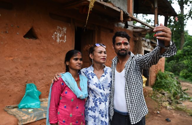 This photo taken on August 22, 2017 shows Nepali transgender person Monika Shahi Nath Yogi (C) posing with her husband Ramesh Nath Yogi and his first wife Laxmi Nath Yogi (L) at Kain Pani village in Nepal's Dadeldhura district. Monika Shahi Nath, 40, became Nepal's first transgender person to be issued with a marriage certificate by district officials when she married 22-year-old Ramesh Nath Yogi in May, even though Nepal has no formal laws for such unions. The couple have found a rare acceptance in Nepal, where many transgender people still struggle to be open about their identity despite progressive laws that include a third gender option on identity cards and passports. / AFP PHOTO / Prakash MATHEMA / TO GO WITH Nepal-transgender-marriage-rights        (Photo credit should read PRAKASH MATHEMA/AFP/Getty Images)