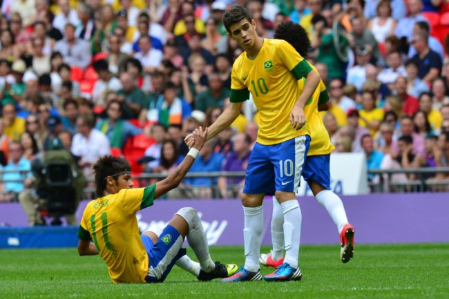 Brazil's midfielder Oscar (R) helps Brazil's forward Neymar to stand up as they play in the men's football final match between Brazil and Mexico at Wembley stadium during the London Olympic Games on August 11, 2012. AFP PHOTO / LUIS ACOSTA (Photo credit should read LUIS ACOSTA/AFP/GettyImages)