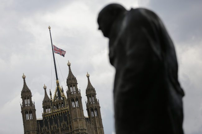 A statue of British former prime minister Winston Churchill, is seen next to a union flag flying at half mast from the roof of the Houses of Parliament in honour of slain Labour MP Jo Cox in London on June 17, 2016. Labour MP Jo Cox, a 41-year-old former aid worker also known for her advocacy for Syrian refugees, was killed on June 16, outside a library where she was supposed to meet constituents in Birstall in northern England, just a few miles (kilometres) from where she was born.  / AFP / Daniel Leal-Olivas        (Photo credit should read DANIEL LEAL-OLIVAS/AFP/Getty Images)