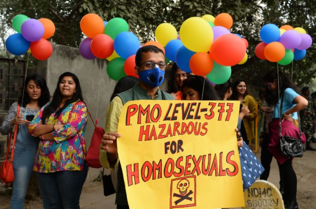 An Indian supporter of the lesbian, gay, bisexual, transgender (LGBT) community wearing a pollution mask hold a placard as he takes part in a pride parade in New Delhi on November 12, 2017. Hundreds of members of the LGBT community marched through the Indian capital for the 10th annual Delhi Queer Pride Parade.   / AFP PHOTO / SAJJAD HUSSAIN        (Photo credit should read SAJJAD HUSSAIN/AFP/Getty Images)