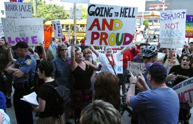 "SEATTLE - MAY 1: Protestors hold signs and greet participants to a rally to affirm traditional marriage between a man and a woman on May 1, 2004 at Safeco Field in Seattle. The special speaker was James Dobson, founder of the evangelical Christian group called ""Focus on the Family"". The event was organized by local Christian groups and drew approximately 20,000 people as well as about 3,000 protestors, according to police. (Photo by Ron Wurzer/Getty Images)"