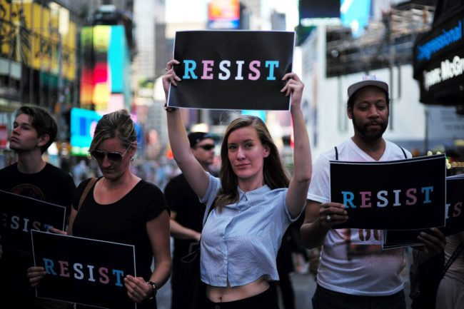 "Protesters display placards against US President Donald Trump during a demonstration in front of the US Army career center in Times Square, New York, on July 26, 2017. Trump announced on July 26 that transgender people may not serve ""in any capacity"" in the US military, citing the ""tremendous medical costs and disruption"" their presence would cause. / AFP PHOTO / Jewel SAMAD (Photo credit should read JEWEL SAMAD/AFP/Getty Images)"