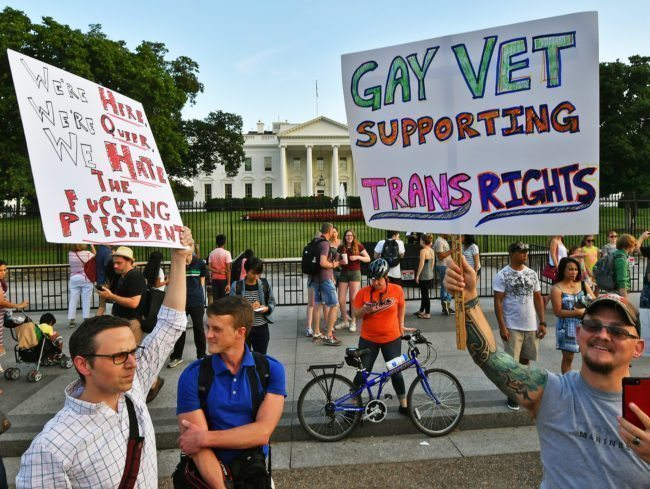 "Protesters gather in front of the White House July 26, 2017, in Washington, DC. Trump announced on July 26 that transgender people may not serve ""in any capacity"" in the US military, citing the ""tremendous medical costs and disruption"" their presence would cause. / AFP PHOTO / PAUL J. RICHARDS (Photo credit should read PAUL J. RICHARDS/AFP/Getty Images)"