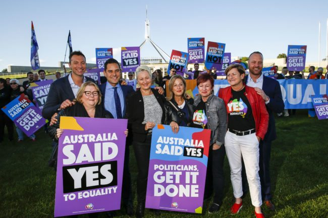 Australian Olympic swimmer Ian Thorpe (L) joins equality ambassadors and volunteers from the Equality Campaign who gather in front of Parliament House in Canberra on December 7, 2017, ahead of the parliamentary vote on Same Sex Marriage, which will take place later today in the House of Representatives.   / AFP PHOTO / SEAN DAVEY