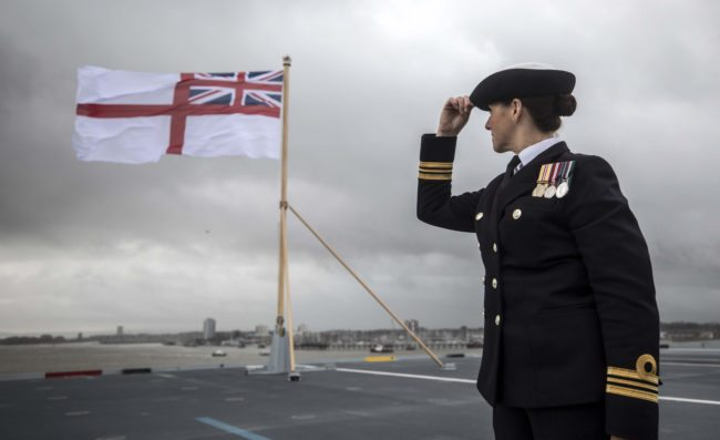 A naval officer looks up at the fluttering White ensign flag hoisted at the stern during the Commissioning Ceremony for the Royal Navy aircraft carrier HMS Queen Elizabeth at HM Naval Base in Portsmouth, southern England on December 7, 2017.  Her Majesty The Queen, accompanied by Her Royal Highness The Princess Royal, attended the Commissioning Ceremony of the aircraft carrier HMS Queen Elizabeth, the largest warship ever built for the Royal Navy.  / AFP PHOTO / POOL / RICHARD POHLE        (Photo credit should read RICHARD POHLE/AFP/Getty Images)