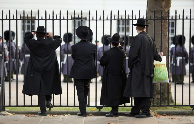 LONDON, ENGLAND - NOVEMBER 05:  Orthodox Jews watch the Grenadier Guards participating in ceremonial duties at Wellington Barracks on November 5, 2009 in London, England. Three Grenadier Gurardsmen were amongst the five soldiers who were shot dead during an attack by a rogue member of the Afghan police force. Two soldiers from the Royal Military Police were also killed.  (Photo by Dan Kitwood/Getty Images)