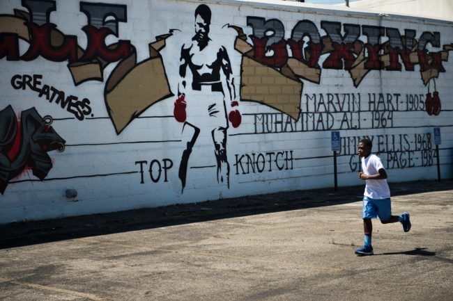 """Curtis Knight, 13, runs laps outside the Louisville TKO Boxing Gymnasium on June 6, 2016 in Louisville, Kentucky. The family of late boxing legend Muhammad Ali and the city of Louisville prepared for his public funeral later this week, which organizers said """"The Greatest"""" helped plan himself as a """"last statement"""" to the world. Ali was born and raised in Louisville, Kentucky. / AFP / Brendan Smialowski (Photo credit should read BRENDAN SMIALOWSKI/AFP/Getty Images)"""